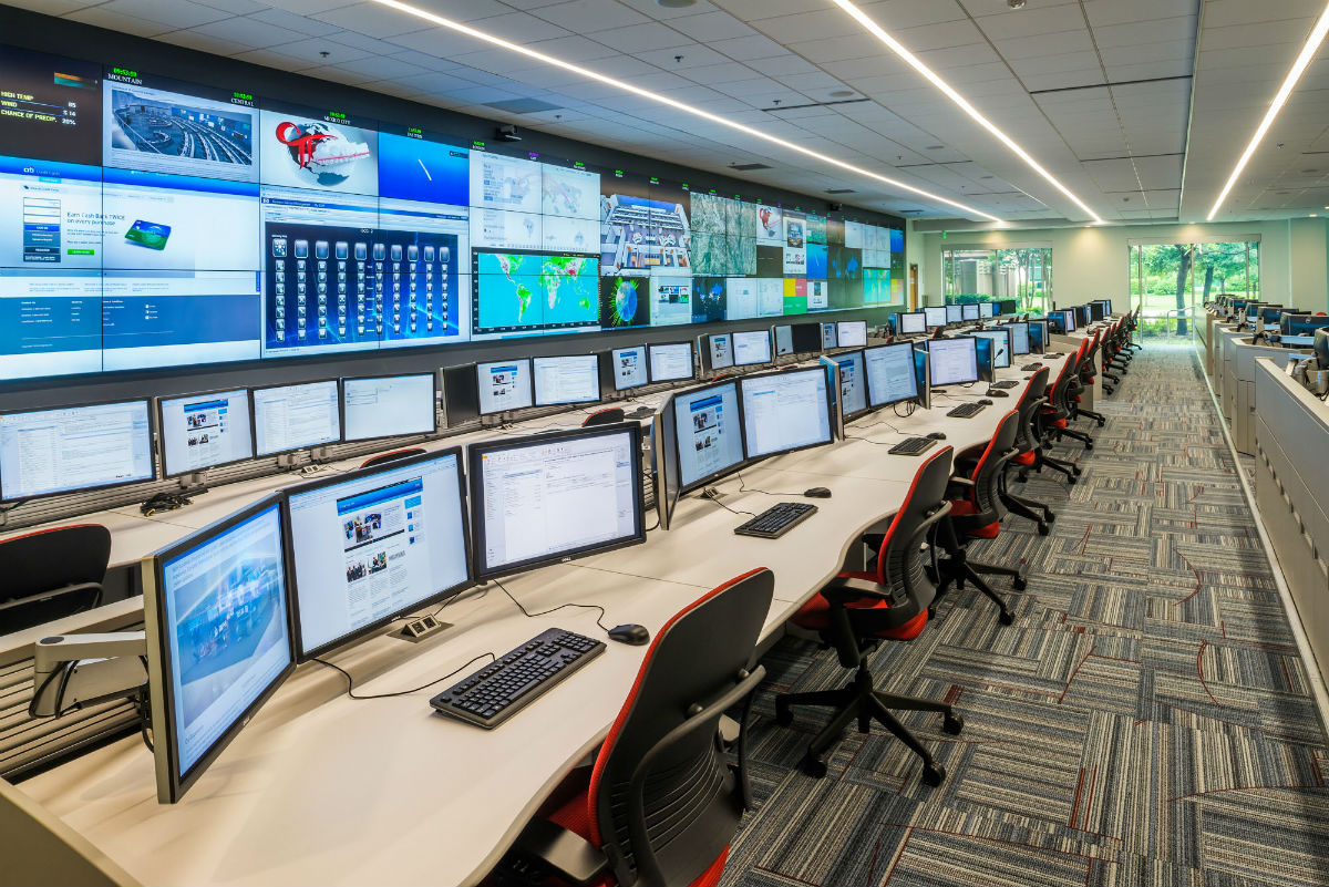 operations center with rows of console furinture and custom video wall