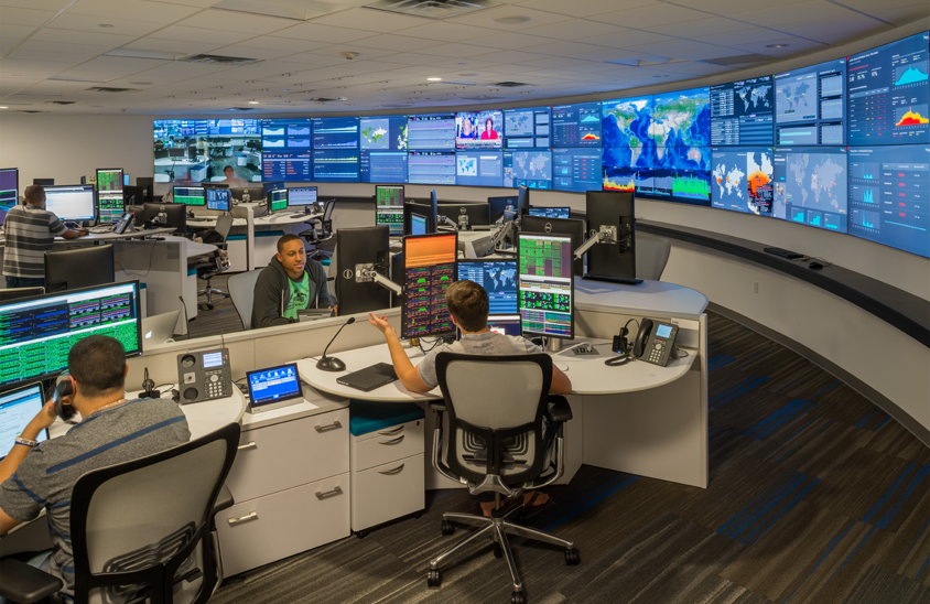 curved video wall in command center with operators talking over their operations center workstations