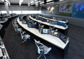 full color rendering of a command and control room for utilities. Features curved rows of console desks and large video wall