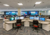 view of two adjacent pod consoles within large operations center facing video wall