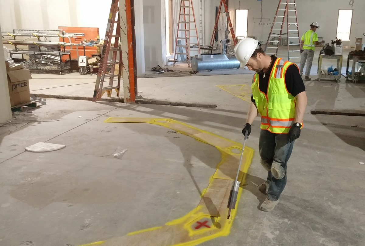 project manager in hardhat and high-vis vest marks out details at construction site