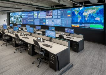 large video wall with rows of custom operations center console desks
