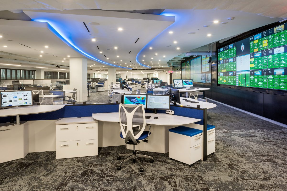 operations center with custom consoles, large video wall, and blue ceiling lighting