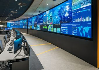 operations center with large video wall and rows of console desks