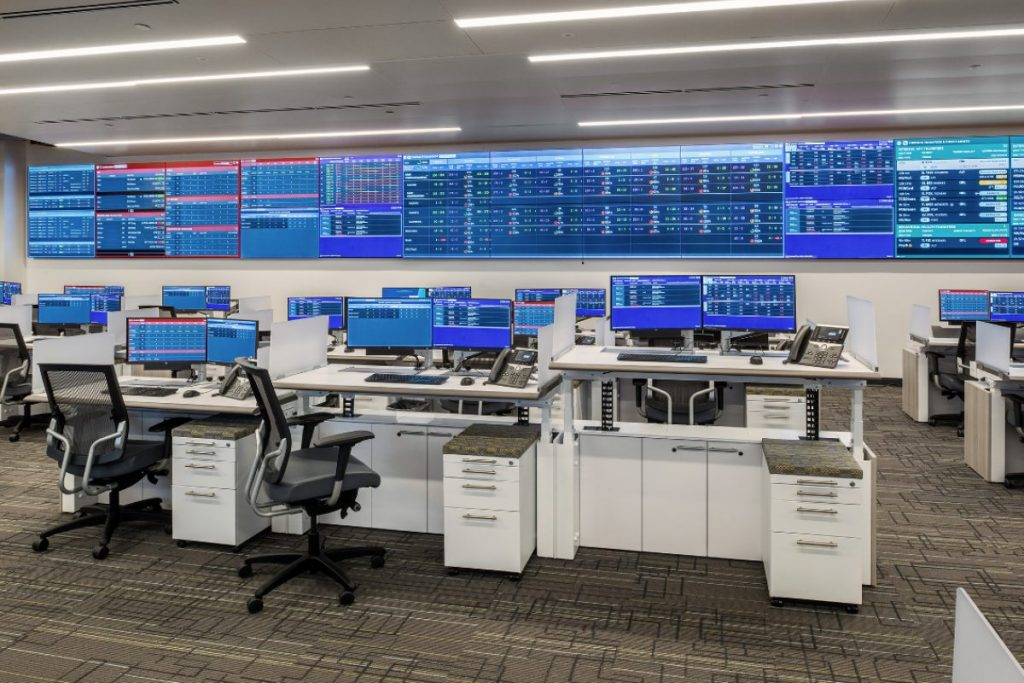 healthcare command center featuring sit-stand adjustable height consoles and large video wall displaying healtchare information