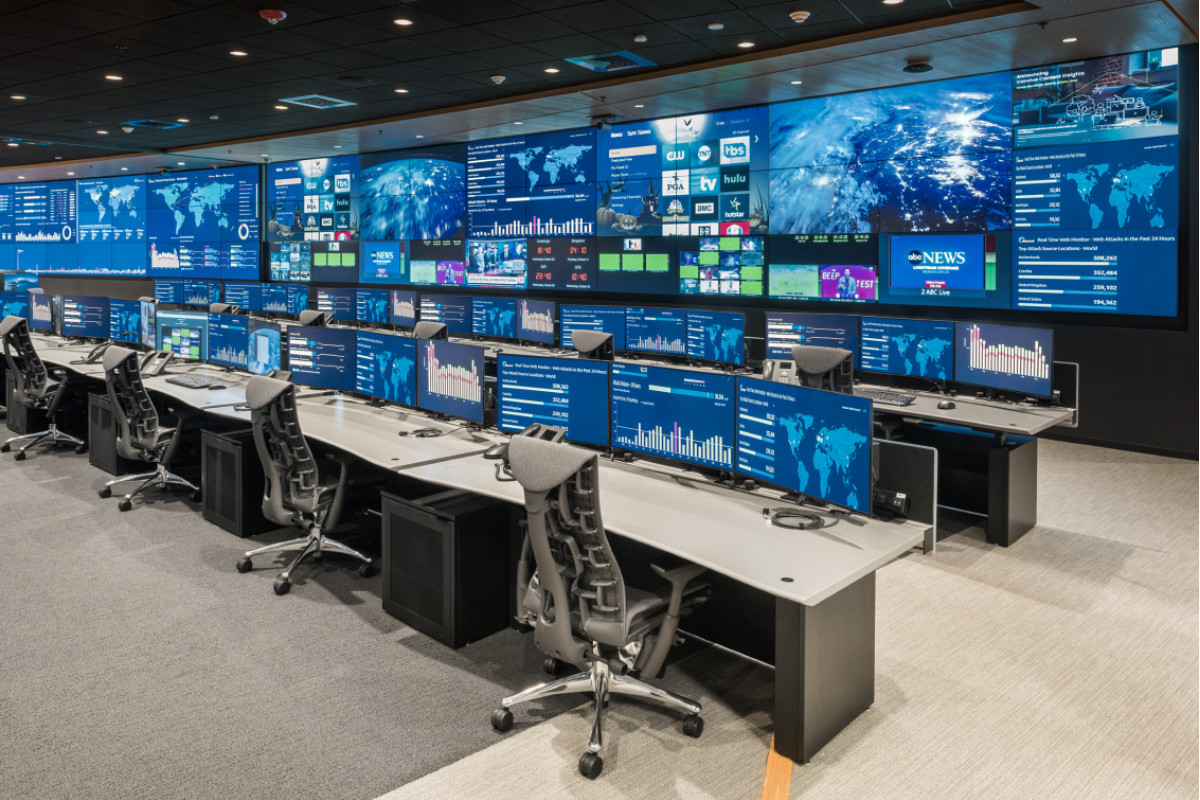 operations center with large central video wall and rows of console furniture