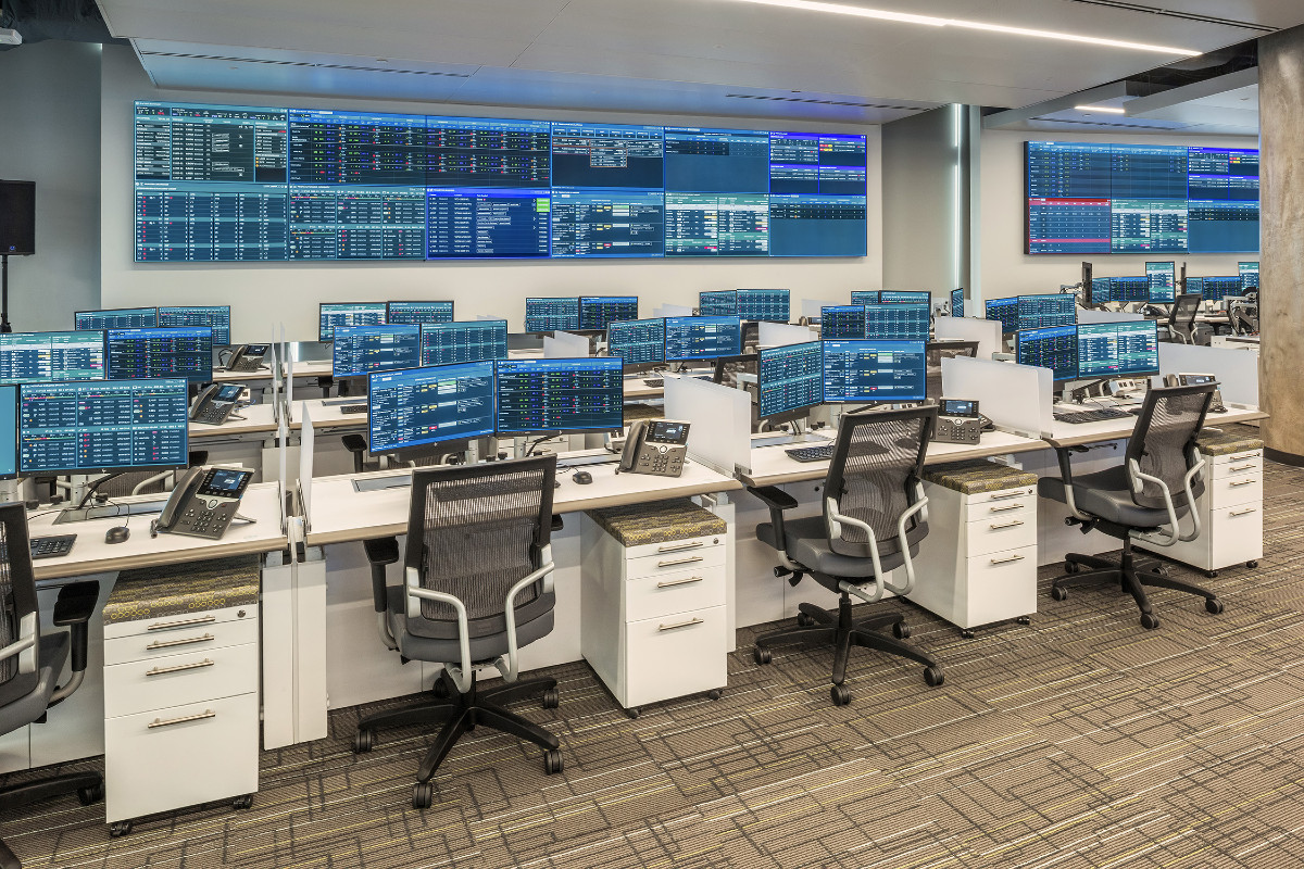 Healthcare operations center with central video wall and rows of console furniture